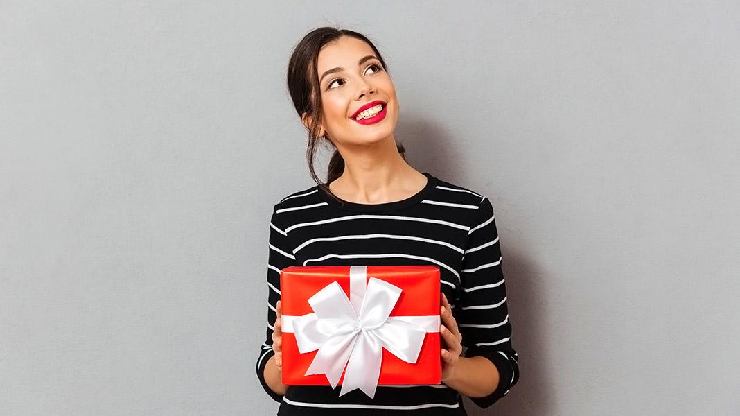 chica sonriente sujetando un regalo