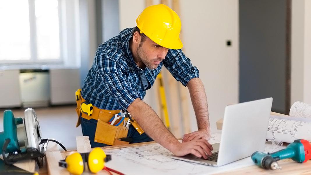 Constructor con casco de protección mirando un ordenador portátil