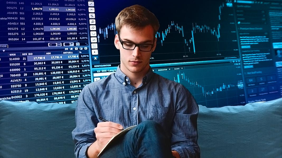chico sentado en un sillón anotando en una libreta, con imágenes de software de trading a sus espaldas