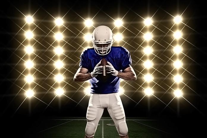 Jugador de fútbol americano concentrado sujetando el balón delante de un panel de focos