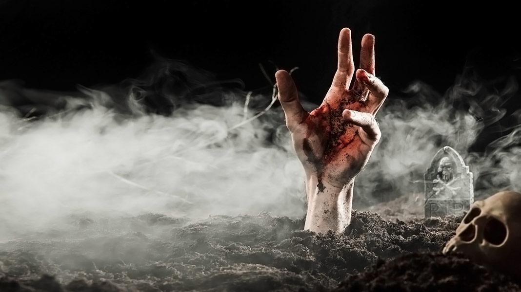 mano saliendo del suelo de un cementerio