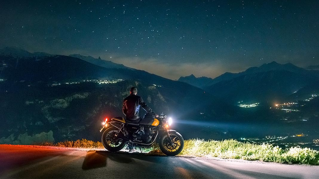 motorista parado de noche en un mirador junto a su moto