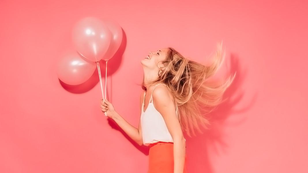 mujer sujetando tres globos rosados