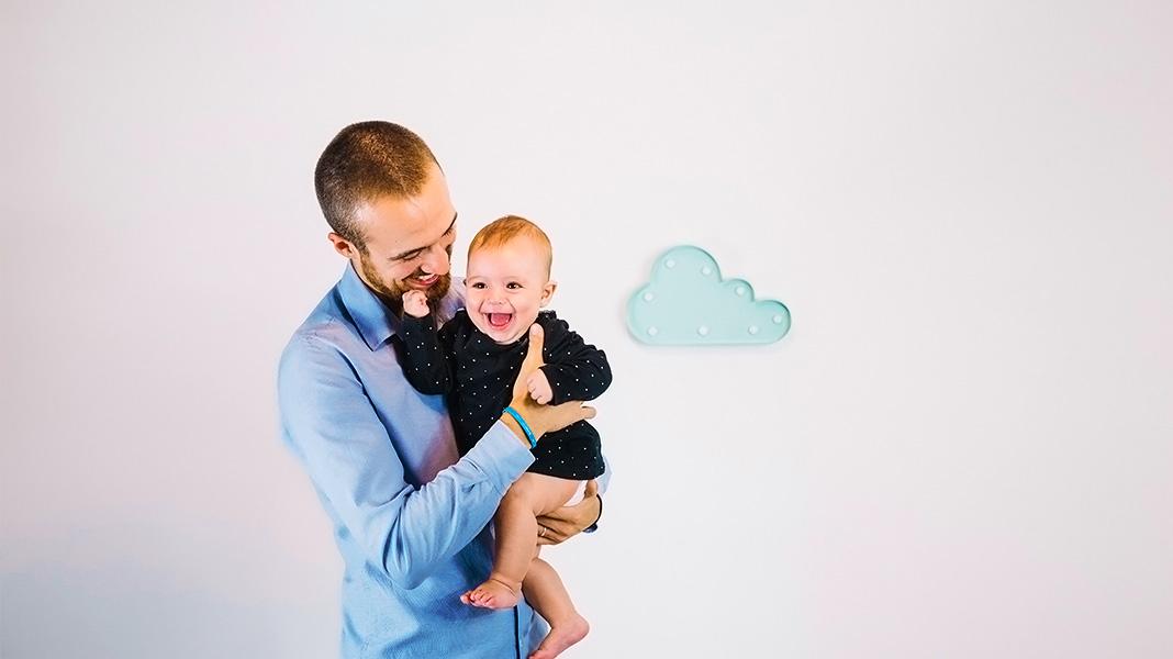 padre joven sujetando a su hijo en brazos