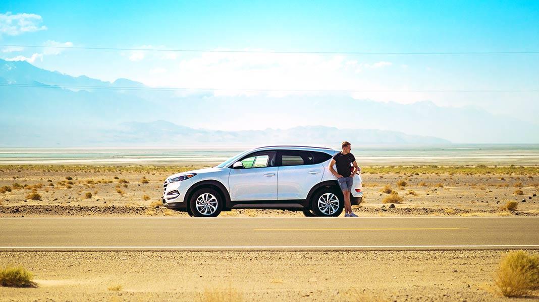 hombre apoyado sobre su coche en una carretera desértica